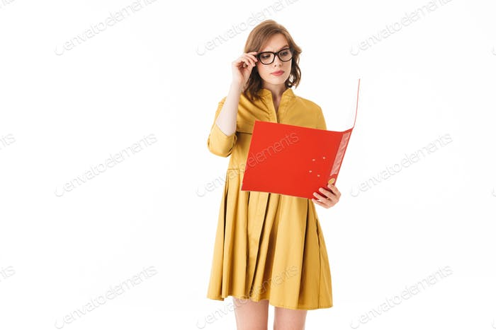 Young lady in eyeglasses and yellow dress standing and thoughtfully lookin in open red folder
