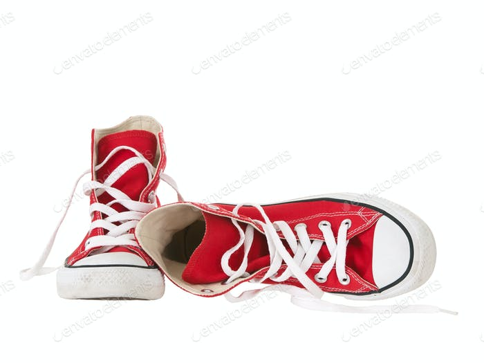 Vintage red sneakers fallen on the ground on white background