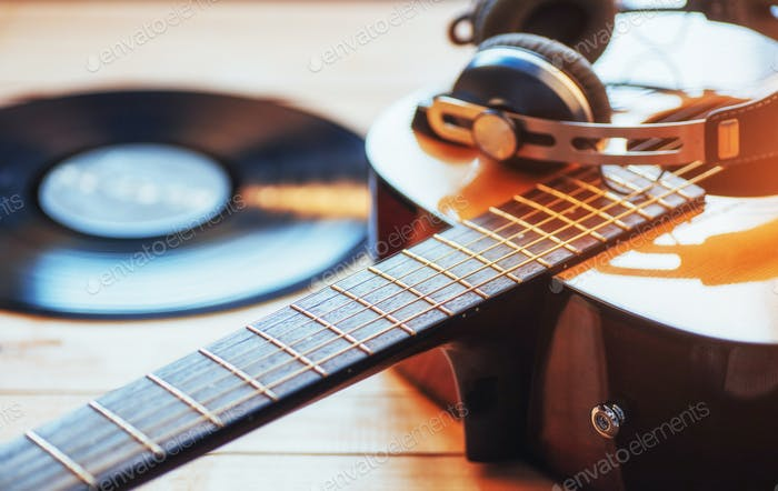 Classical guitar with headphones on a wooden background