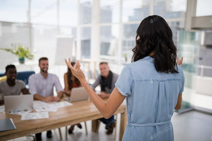 Female executive explaining business plans to his coworkers