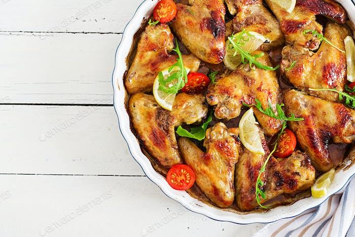 Alitas de  pollo al horno en placa sobre mesa de De madera. Vista superior.