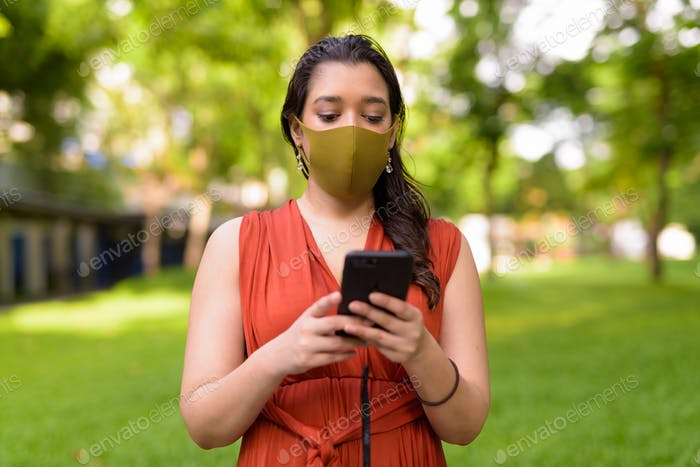 Young Indian woman with mask using phone at the park