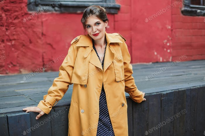 Junge schöne lächelnde Frau in orange Trenchcoat und schwarz po