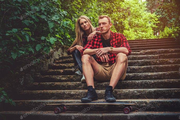 Casual moder junge Skateboarder Paar posiert auf Fußweg.