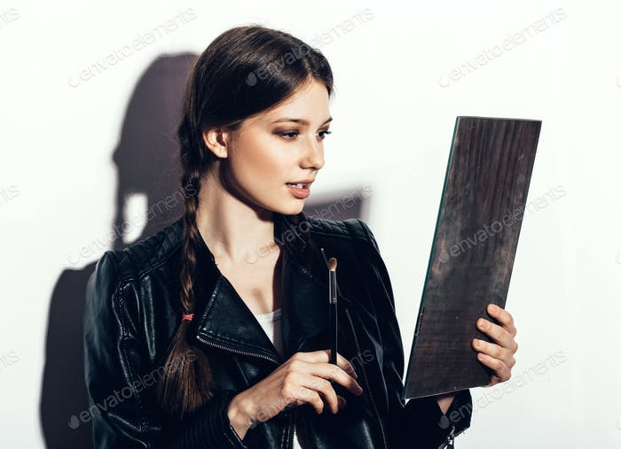 woman looking in the mirror and applying cosmetic