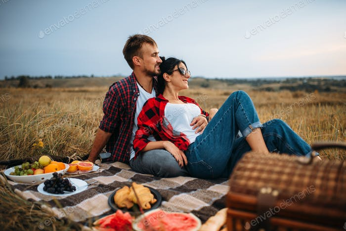 Love couple, picnic on plaid in summer field