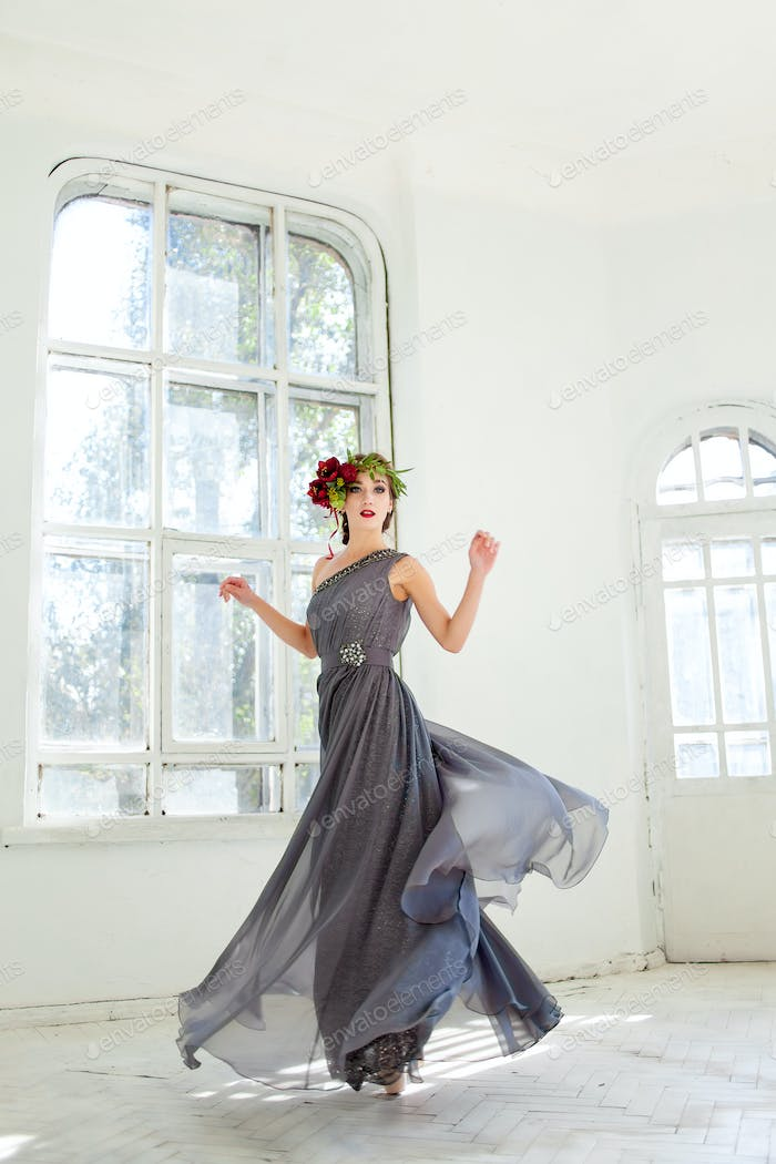 The beautiful ballerina dancing in long gray dress