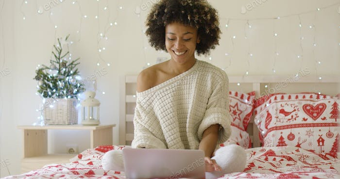 Happy woman in sweater on bed using computer