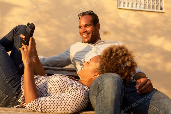 Happy african american couple together on park bench