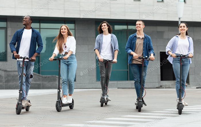 Five students having ride on motorized kick scooters