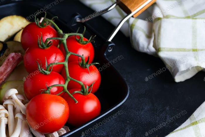 Frische Kirschtomaten Grillpfanne als Kochzutaten für Gericht auf dunklem Hintergrund mit Serviette