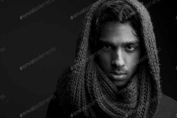 Young man with wool scarf covering head