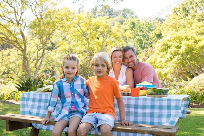 Glückliche Familie sitzt am Tisch im Park