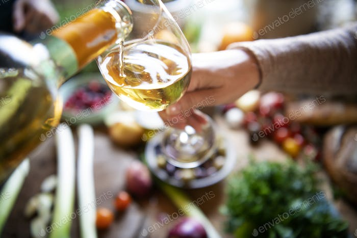 Couple having white wine while cooking