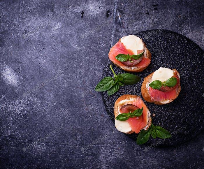 Crostini with salmon, mozarella, tomato and basil