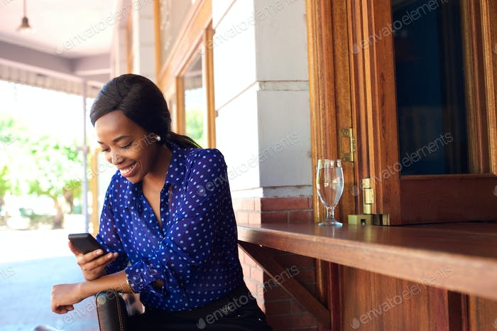 Happy woman sitting at bar smiling with mobile phone