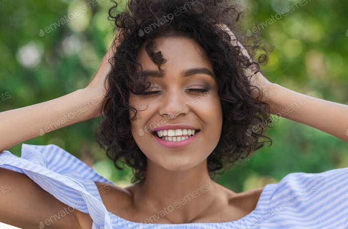 Excited african-american woman having rest in the park