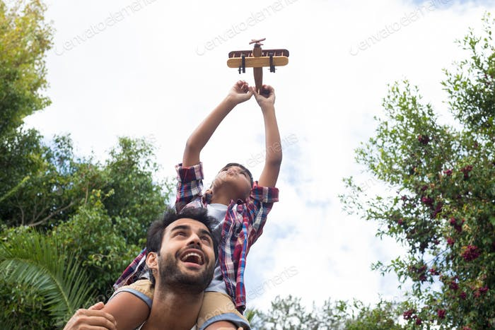 Low angle view of father carrying son playing with airplane