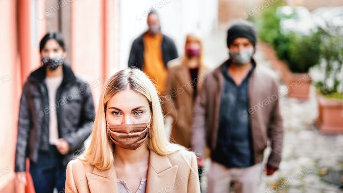 Urban crowd of young people walking on city street covered by face mask