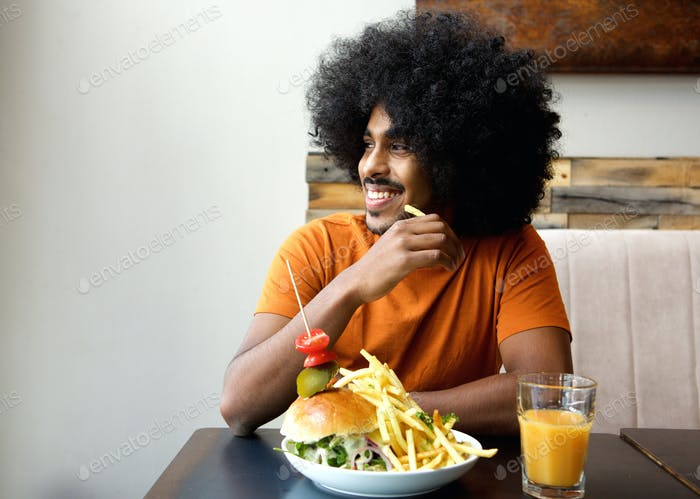 Smiling man with hamburger and fries at restaurant