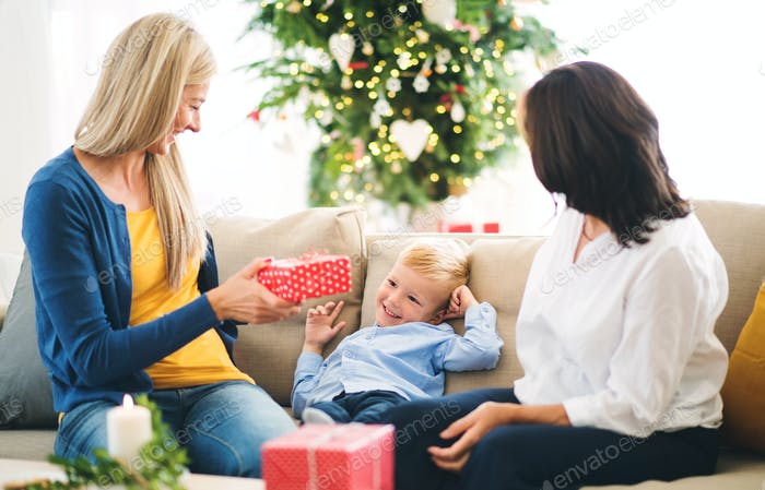 A mother and grandmother giving presents to a small boy at home at Christmas time.