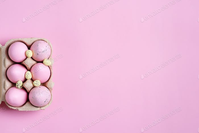 Festive Easter frame from paper box of handmade pink painted eggs on a same color background