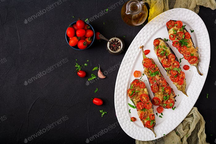 Baked eggplants with mozzarella and tomatoes with Italian herbs. Flat lay. Top view