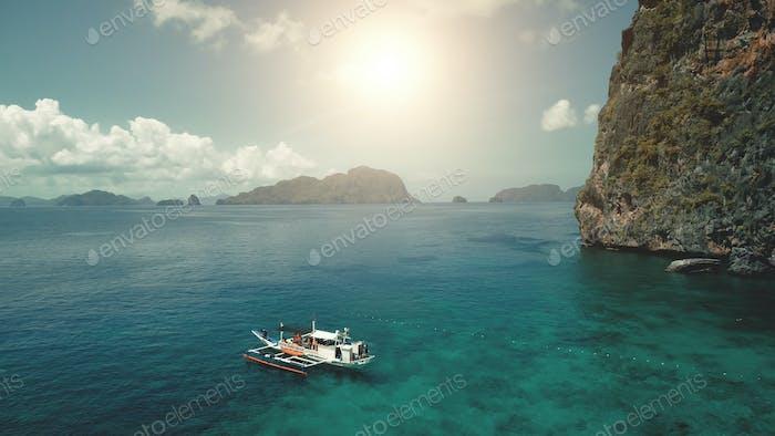 Closeup passenger ship at sea coast with green cliff shore at sun summer day vacation