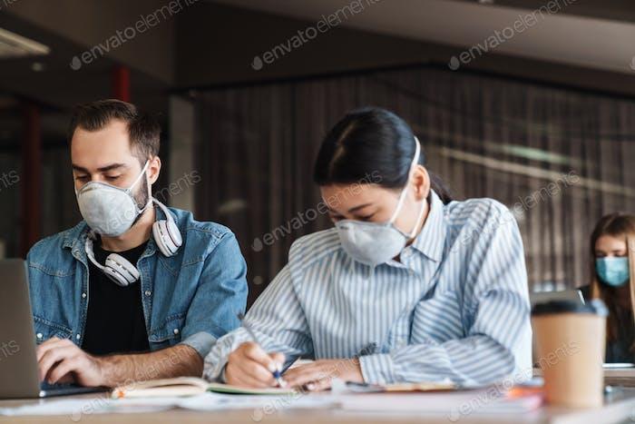 Foto von multinationalen Studenten in medizinischen Masken, die mit Laptop studieren