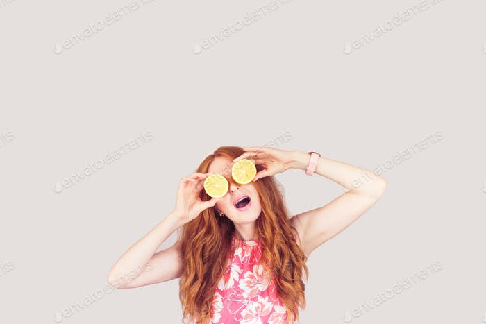Red-hair woman keep two lemons on her eyes