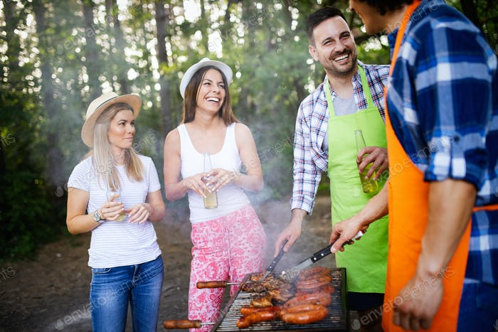 Group of happy friends having a barbecue party in nature