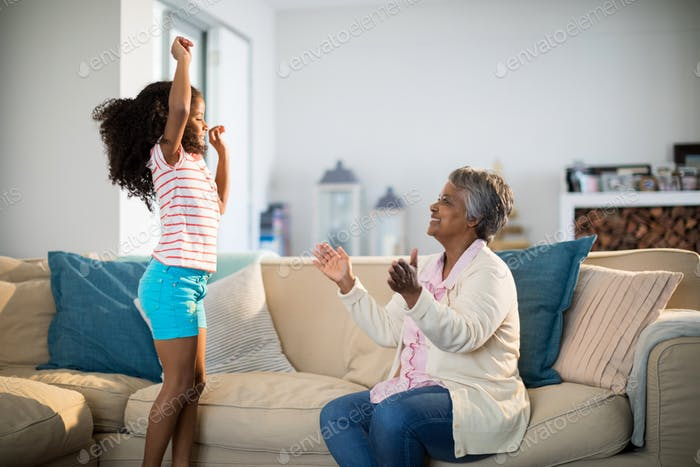 Grandmother applauding her granddaughter while dancing in living room