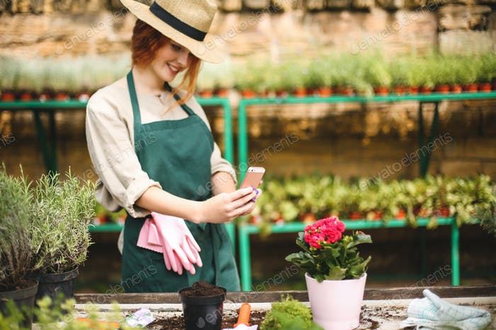 Young pretty florist in apron and hat standing and taking photos of flower in pot on her cellphone