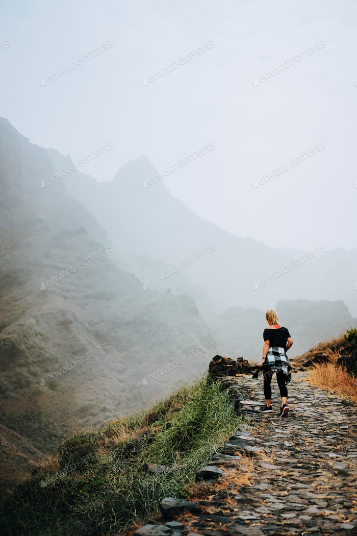 Santo Antao Island, Cape Verde. Tourist female on stony hiking path to Ponta do Sol over arid