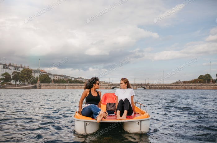 Two young women friends sitting in front pedal boat