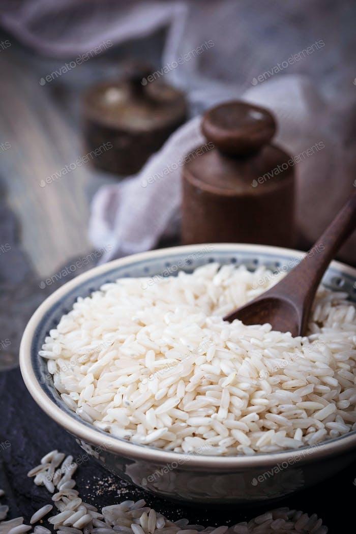 Weißer ungekochter Reis auf Betonuntergrund