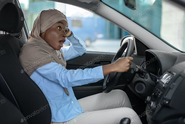 Shocked african muslim woman having car accident, her auto hit by another vehicle