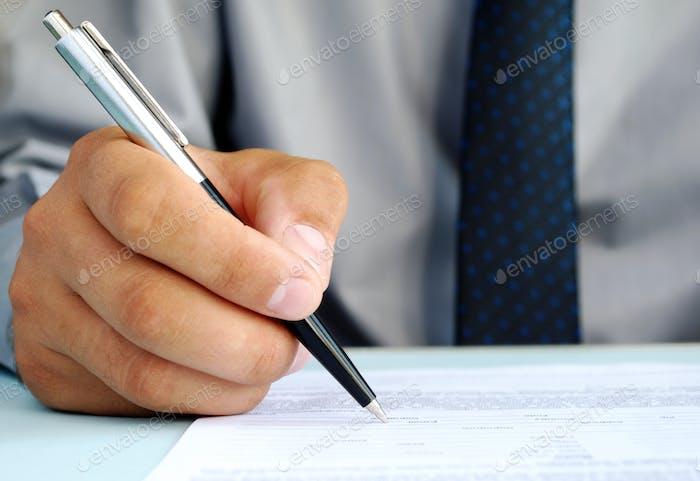 Hand eines Mannes und eines Kugelschreibers