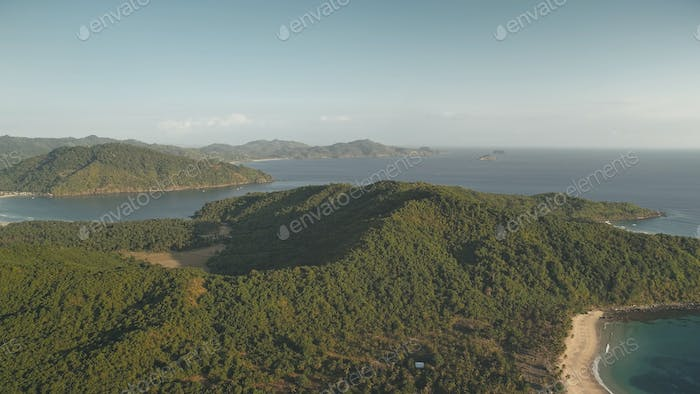 Nobody tropic islands landscapes at sea bay aerial. Green forest on mount at ocean shore. Palm trees