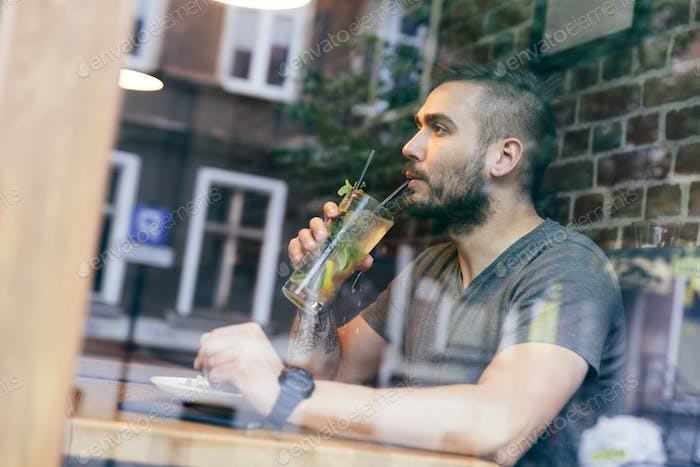 Man drinking cold fit beverage in a cafe.