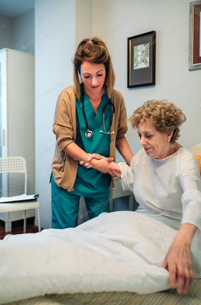 Сиделка помогает пожилому пациенту встать с постели