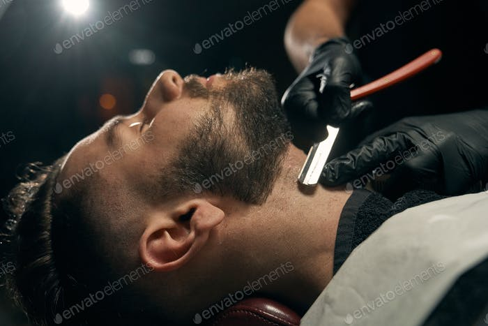 Close up of barber's hands shaving beard for client