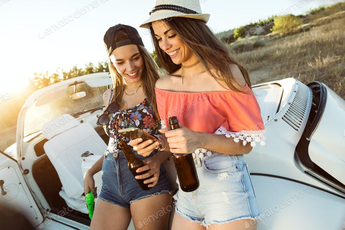 Two beautiful young women using mobile phone on road trip.