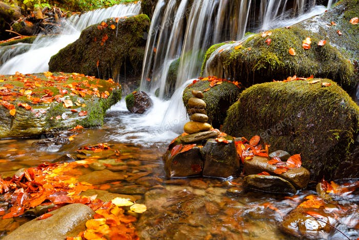 Beautiful landscape with a waterfall in the autumn forest