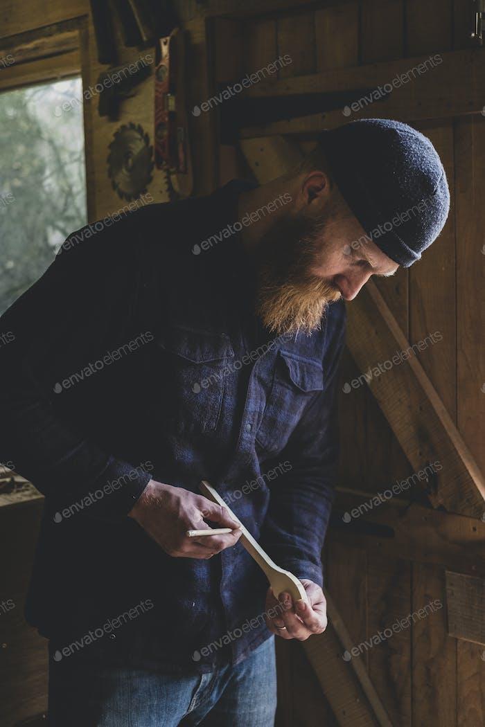 Bearded man wearing black beanie standing in workshop, examining piece of wood.