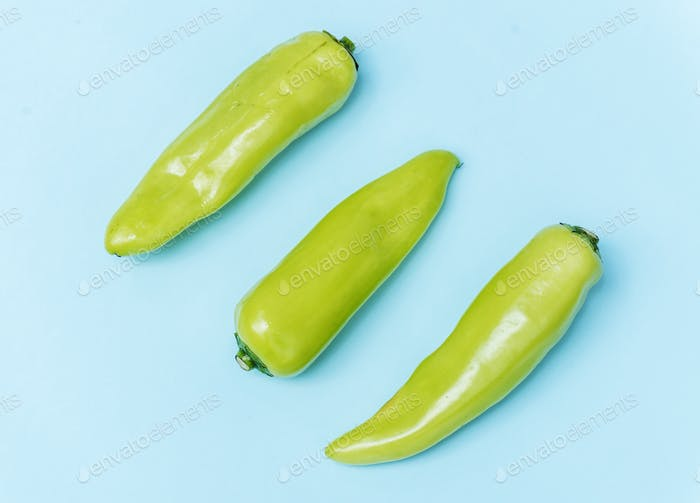Aerial view of fresh jalapeno peppers on blue background