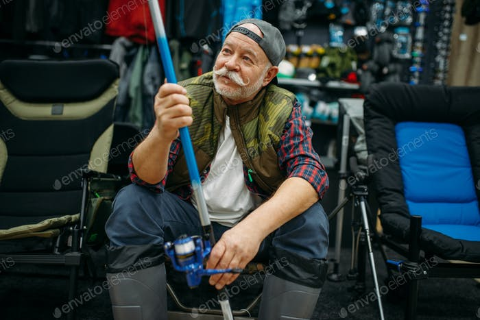 Angler in rubber boots holds rod in fishing shop