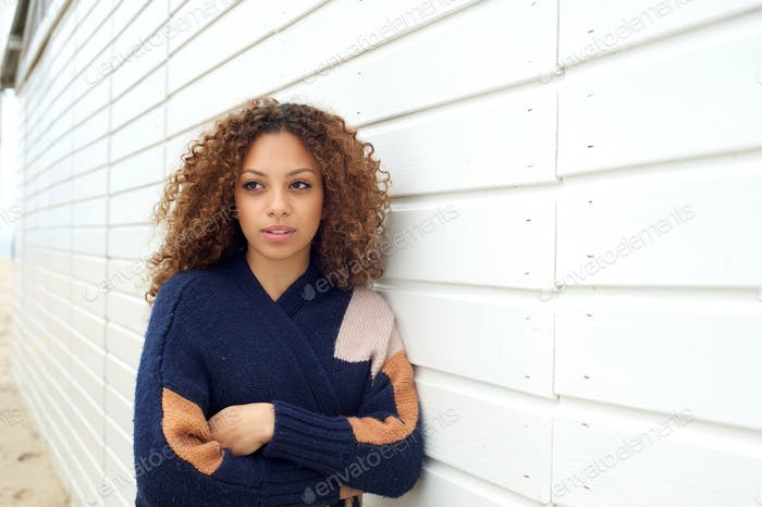Beautiful young woman with curly hair and sweater posing outdoors