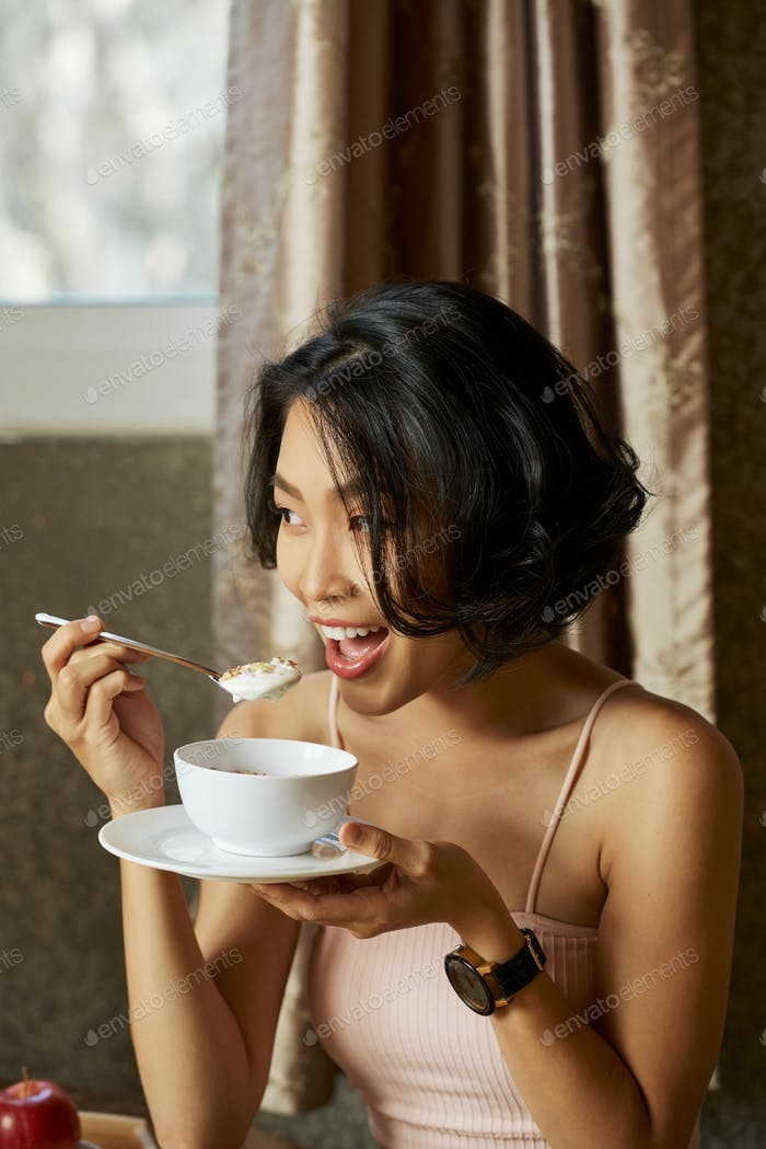 Frau essen Joghurt mit Müsl