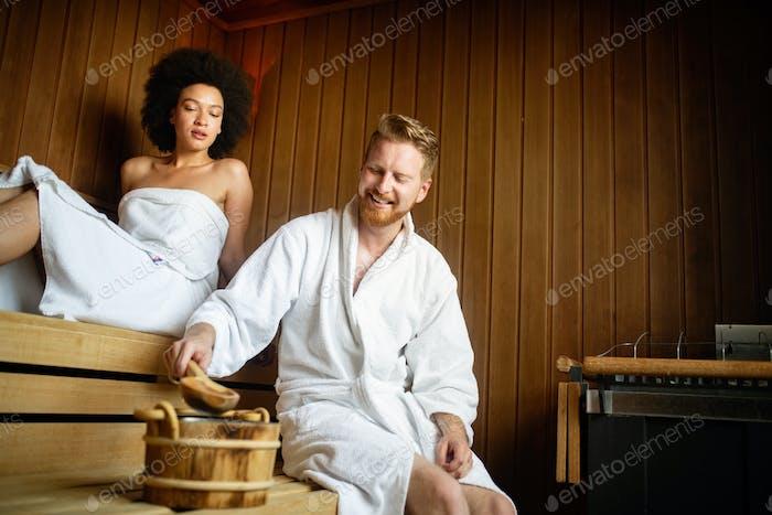 Pareja feliz teniendo un baño de vapor en una sauna